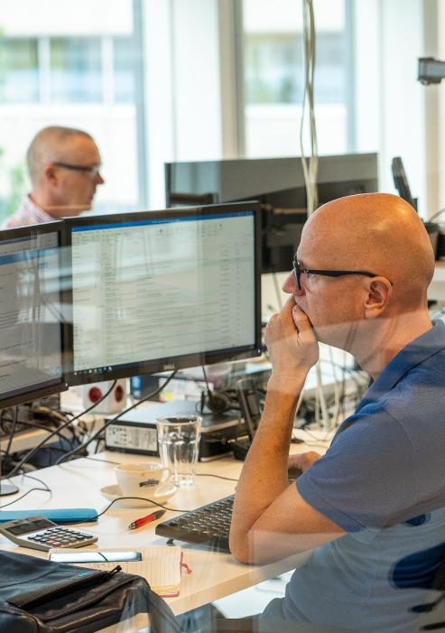 Twee medewerkers in gedachte achter hun computers